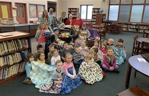 Picture of students wrapped in blankets that were made and donated.
